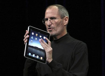 "Apple CEO Steve Jobs holds the new "" iPad"" during the launch of Apple's new tablet computing device in San Francisco"
