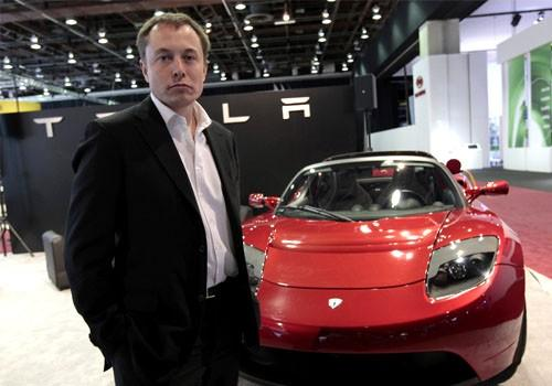 Tesla CEO Elon Musk stands in front of the Tesla Roadster