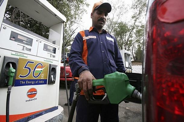 An employee fills a car with petrol at a gas station in Jammu February 26, 2010. India will raise petrol and diesel prices from Friday midnight, Oil Secretary S. Sundareshan told reporters.