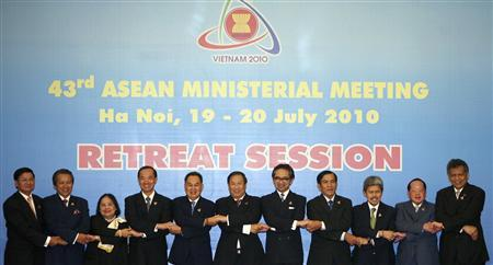 ASEAN Foreign Ministers join hands as they pose for a photo