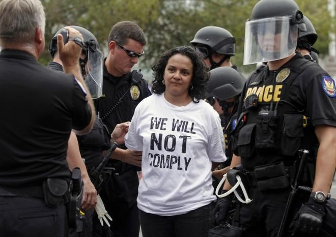 A demonstrator is arrested during a protest against Arizona's controversial Senate Bill 1070 immigration law outside the U.S. District Court in Phoenix July 22, 2010.
