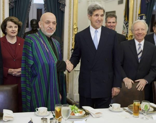 Afghan President Hamid Karzai (2nd L) shakes hands with Senator John Kerry (D-MA) during a luncheon hosted by the Senate Foreign Relations Committee