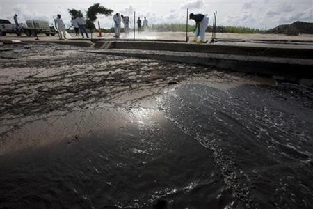 Workers pressure-wash oil from the Deepwater Horizon spill from a roadway in Waveland, Mississippi