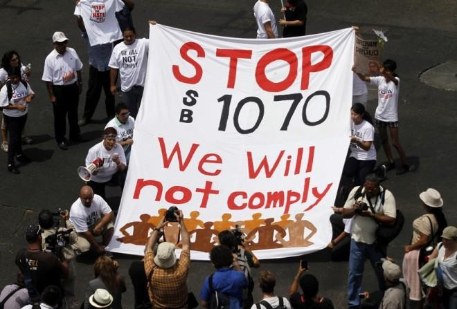 Demonstrators hold a banner as they protest against Arizona's controversial Senate Bill 1070 immigration law outside the U.S. District Court in Phoenix July 22, 2010.