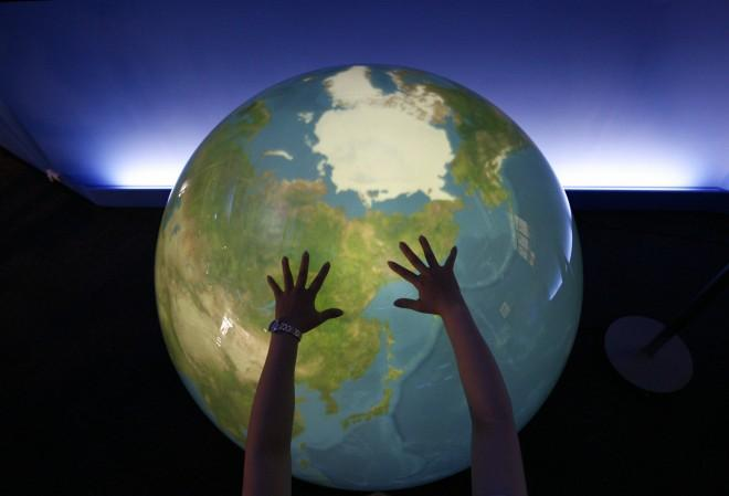 A visitor places her hands on a tangible earth, a digital globe, at an exhibition pavillion in Rusutsu town, northern Japan.