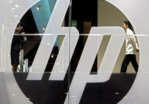 An employee walks past a Hewlett-Packard logo