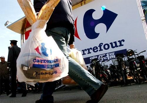 A Chinese man carries grocery bags after shopping at french hypermarkert Carrefour in Beijing, China