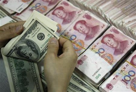 File photo of an employee counting U.S. dollar banknotes as yuan banknotes are seen at a branch of the Industrial and Commercial Bank of China in Huaibei