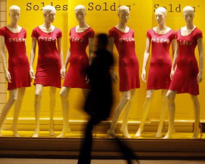 A shopper walks past a clothing store window advertising sales in Nice
