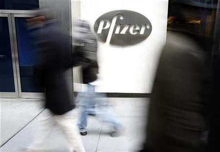 People walk past the Pfizer World headquarters in New York