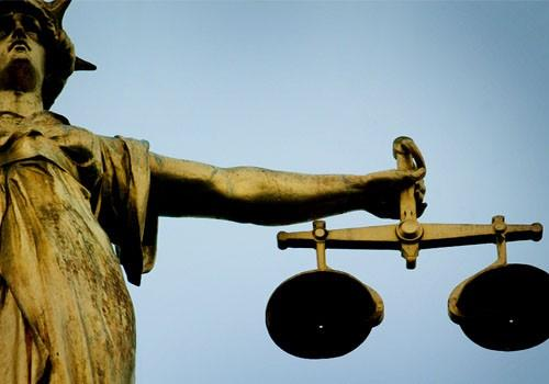 A statue holding the scales of justice is seen on top of the Old Bailey in London