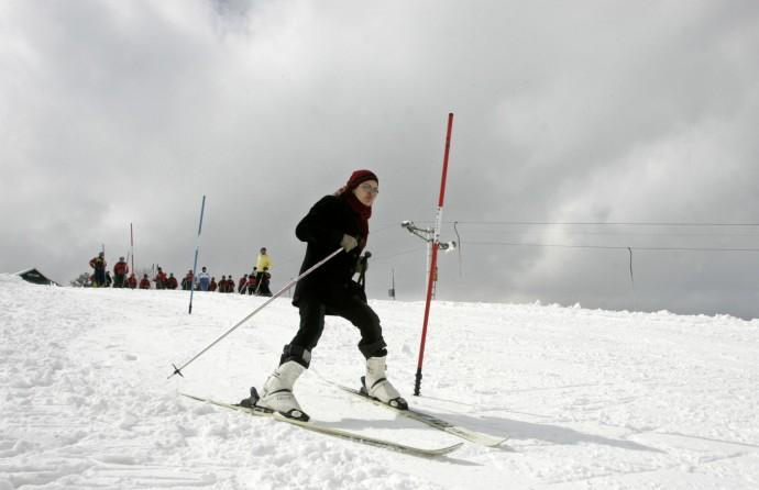 A woman learns to ski on a slope in Gulmarg