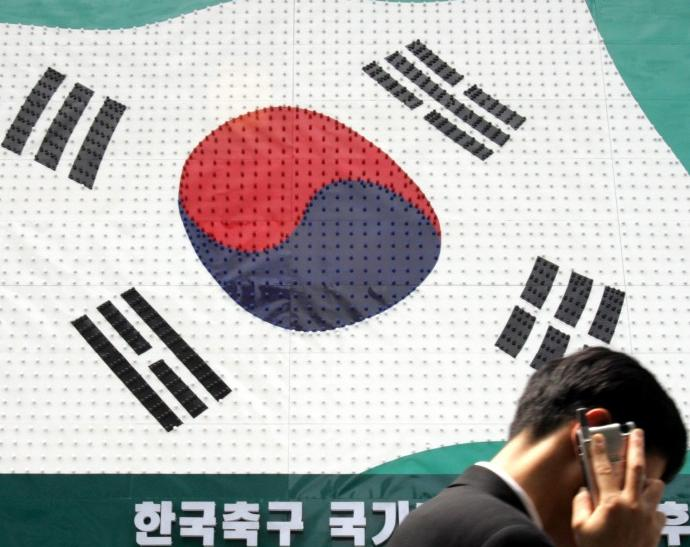 A man walks past a sign resembling a South Korean flag in Seoul