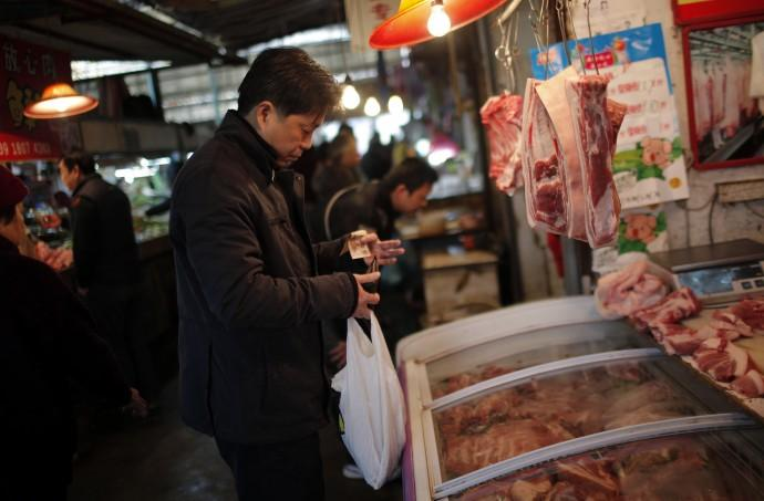 A man buys meat at a local food market in Shanghai