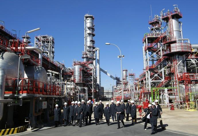 Spain's King Juan Carlos walks with members of Cepsa during his visit to a Cepsa refinery in Palos de la Frontera