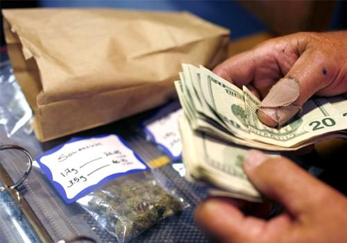A customer makes a medical marijuana purchase at the Coffeeshop Blue Sky dispensary in Oakland, California June 30, 2010