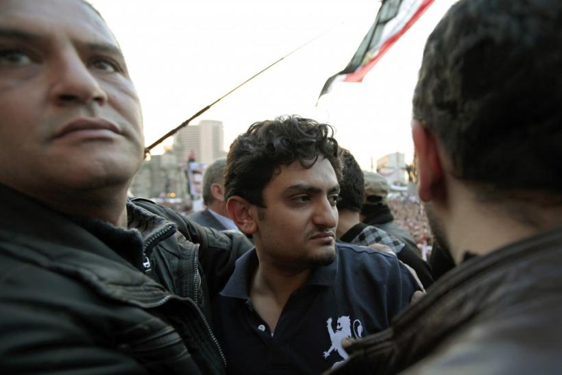 Google Inc executive Wael Ghonim is escorted through a mass crowd inside Tahrir Square in Cairo