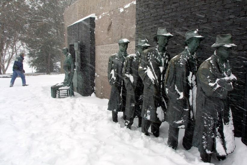 A driving blizzard blows on a Great Depression Bread-Line sculpture as a hiker walks by at the FDR Memorial in Washington