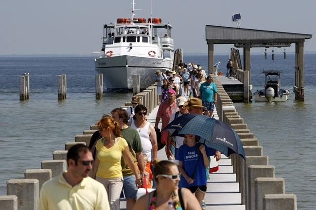 Tourists arrive to spend the day on West Ship Island, as BP contractors laid boom offshore to contain an oil spill off the coast of Gulfport, Mississippi May 6, 2010.