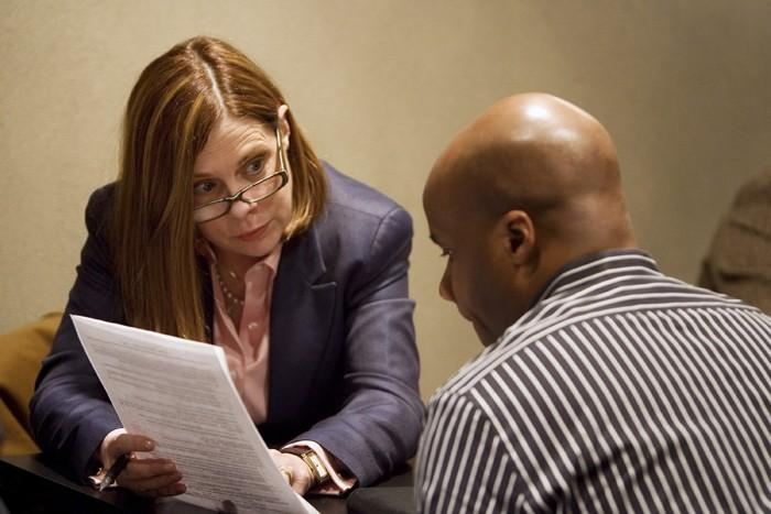 A job seeker listens to a career coach, Jane Cranston during a resume counselling session at a job fair in New York