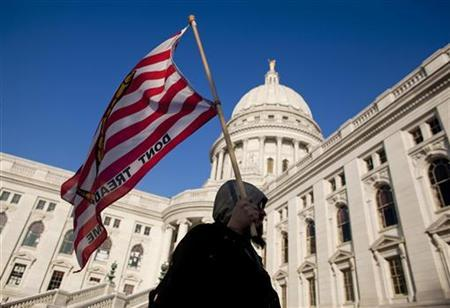 A man marches with a flag while protesting outside the state Capitol in Madison