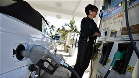 A resident looks at the price of gasoline as she fuels up her car at a gas station in South Beach