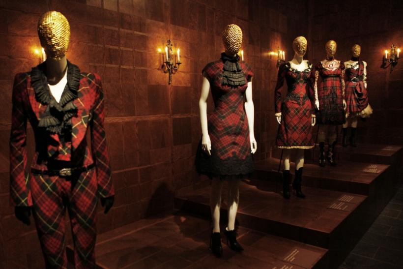 Visitors look through a glass display case at creations by the late British designer Alexander McQueen during a preview at the Metropolitan Museum of Art in New York