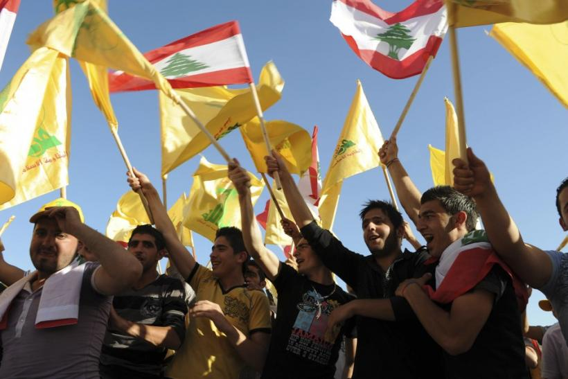 Supporters of Lebanon's Hezbollah wave Lebanese and Hezbollah flags as they listen to a televised address by Sayyed Hassan Nasrallah during a rally in Nabi sheet