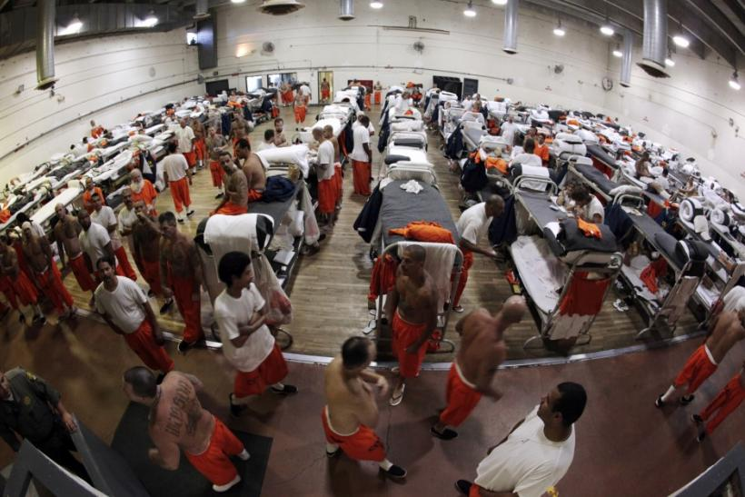 Inmates walk around a gymnasium where they are housed due to overcrowding at the California Institution for Men state prison in Chino