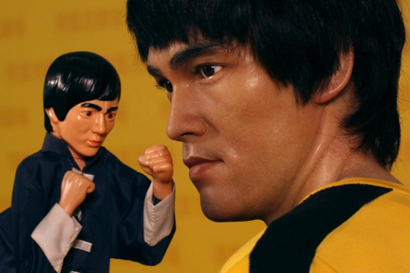 A hand puppet is placed next to a life-sized wax figure of the late Bruce Lee during an exhibition which celebrated the works of the martial arts legend at a shopping mall in Hong Kong
