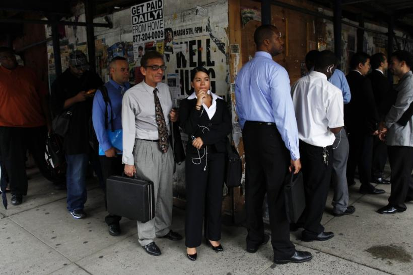 People wait in line to enter a job fair in New York
