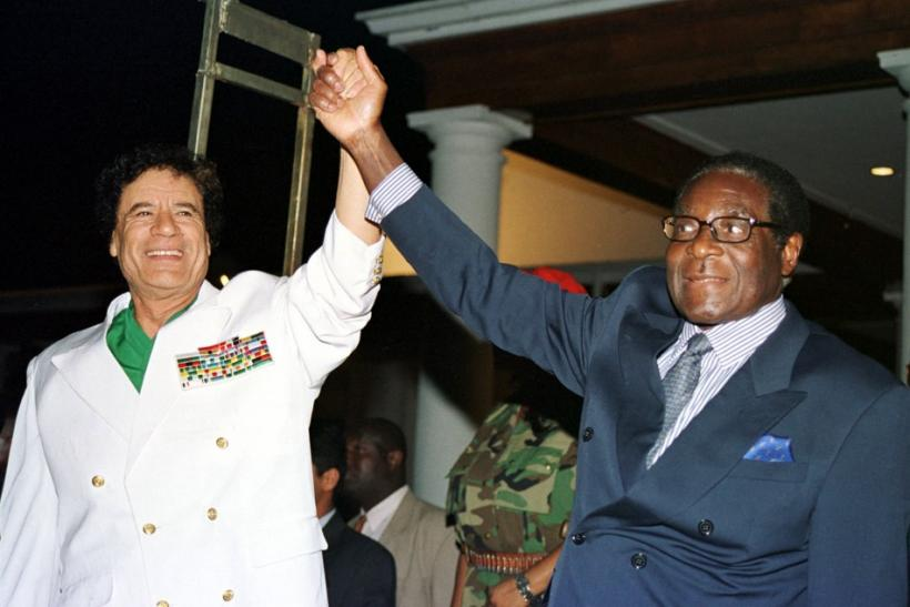 Libyan leader Colonel Muammar Gadaffi (L) and Zimbabwe President Robert Mugabe greet supporters outside State House in Harare July 12, 2001.