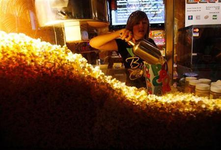 Cailynn Williams, 17, fills a bag of popcorn for a customer at the New Strand Theater in West Liberty
