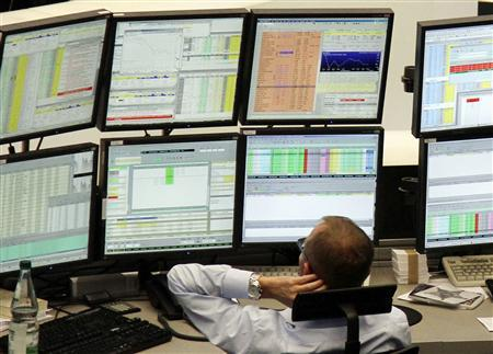 A trader is pictured at his desk in front of the DAX board at the Frankfurt stock exchange