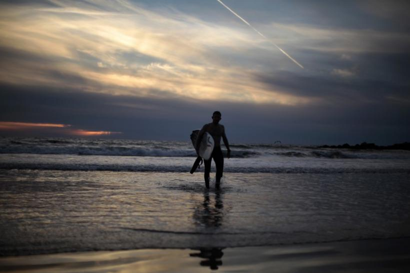 A surfer walks out of the ocean as the sun sets on New Year's Eve on Venice Beach in Los Angeles