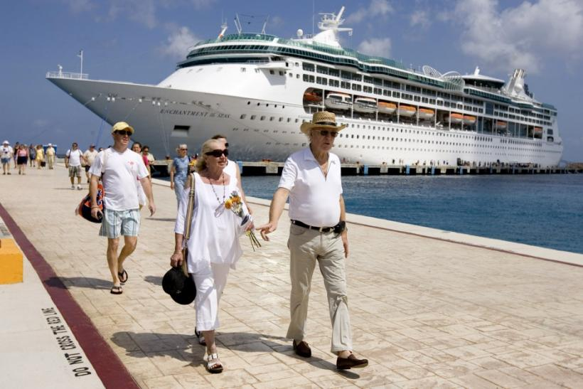 Tourists walk beside Royal Caribbean's cruise ship ?Enchantment of the Seas? after they arrive