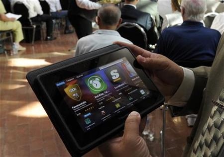 A man holds a BlackBerry PlayBook during the RIM annual general meeting of shareholders in Waterloo