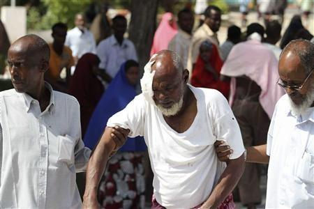 People assist a man wounded in a suicide blast in Mogadishu