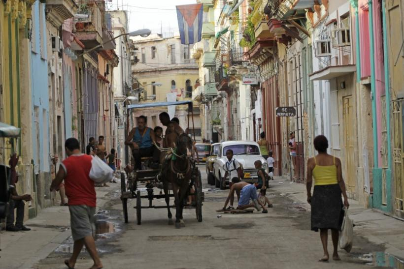 People walk as children play on a street in Havana, Cuba