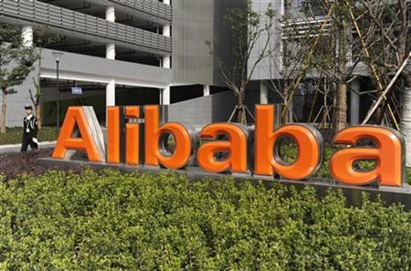 A security guard walks past a logo of Alibaba (China) Technology Co. Ltd at its headquarters on the outskirts of Hangzhou