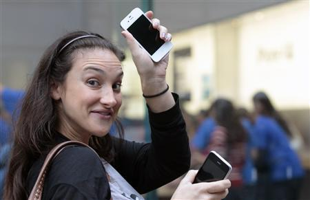 A customer shows off her new iPhone 4S as she leaves an Apple Store in New York