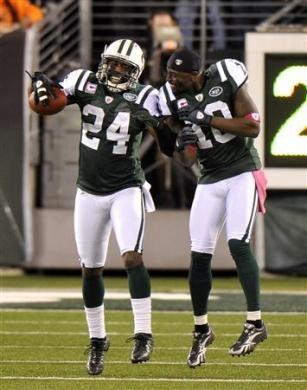 New York Jets' Darrelle Revis (L) celebrates with teammate Santonio Holmes after Revis returned an interception for a touchdown against the Miami Dolphins in the first half of their NFL game in East Rutherford, New Jersey