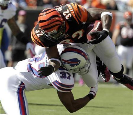 Cincinnati Bengals' running back Cedric Benson (32) is tackled by Buffalo Bills' George Wilson (37) during the first half of play in their NFL football game at Paul Brown Stadium in Cincinnati, Ohio