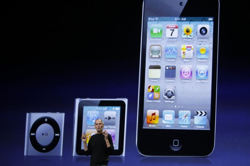 Apple Chief Executive Steve Jobs speaks on stage, with images of the iPod Shuffle (L-R), iPod Nano and iPod Touch projected onscreen, at Apple's music-themed September media event in San Francisco, California September 1, 2010.