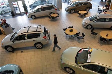 A customer looks over Toyota automobiles at a dealership in Daly City, California