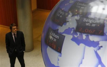 A man stands next to a globe displaying international stock market prices at the London Stock Exchange in the City of London