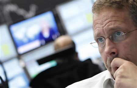 Trader reacts at his desk in front of the DAX board at the Frankfurt stock exchange