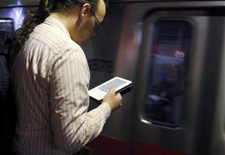 A commuter reads on his Kindle e-reader as a subway train arrives in Cambridge, Massachusetts