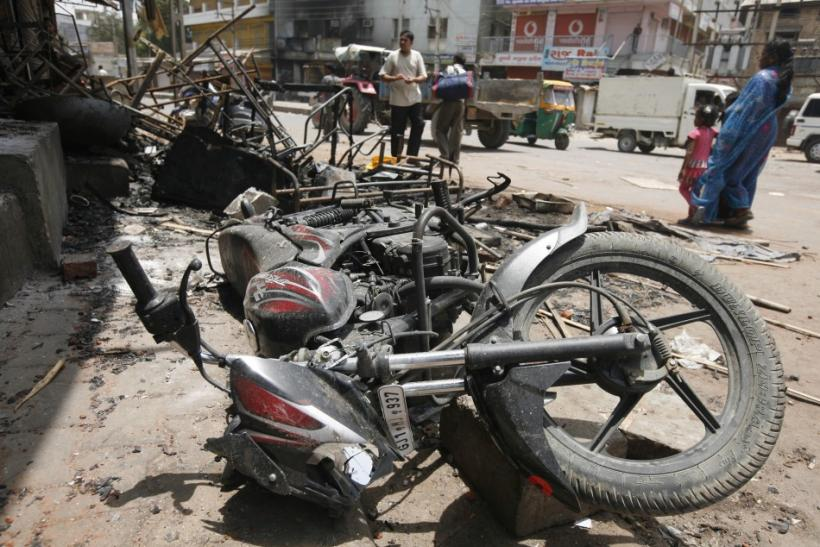 Commuters walk past debris of burnt vehicles after a clash between two communities at Sanand