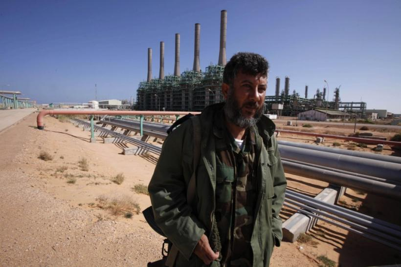 An armed National Transitional Council fighter patrols inside the Libyan Oil Refining Company in Ras Lanuf